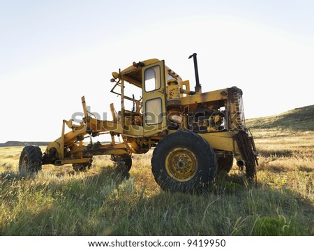 Yellow tractor in field. - stock photo
