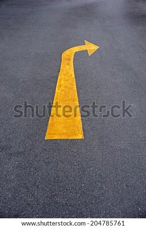 yellow traffic arrow signage on an asphalt road - stock photo