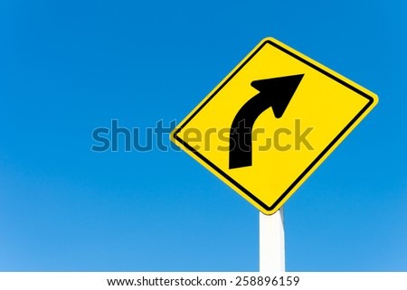 Yellow traffic right curve sign on blue sky background. - stock photo