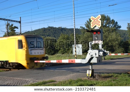 yellow train goes over the railway crossing with gates, Motion blurred train passing a railroad crossing, Czech Republic - stock photo