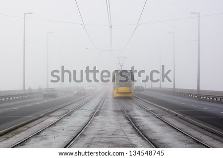 Yellow tram comes in the mist in the bridge - stock photo