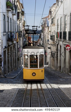 Yellow tram in Lisbon, Portugal, driving in a very steep street, one of the main tourist attractions - stock photo