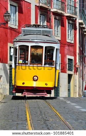 Yellow tram on narrow street, Alfama district of Lisbon. Portugal symbol - stock photo