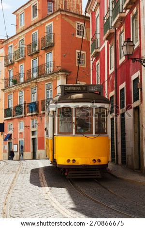yellow tram on narrow street of Alfama, Lisbon, Portugal  - stock photo