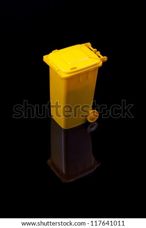 yellow trash, isolated in black - stock photo