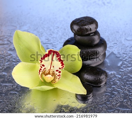 Yellow tropical orchid flower and spa stones on bright background - stock photo