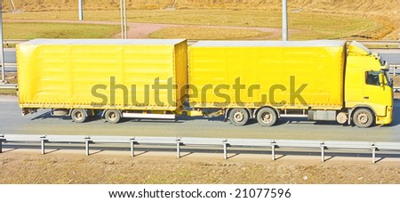 Yellow truck delivering import goods - stock photo