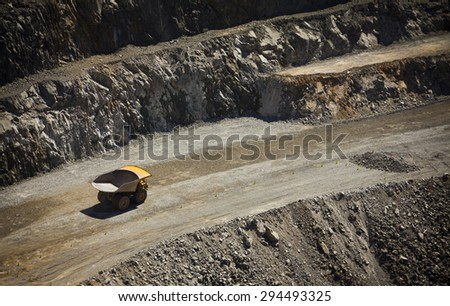 Yellow truck drives along a dirt road in an open cast mine in New South Wales, Australia. Barrick Cowal Gold Mine. - stock photo