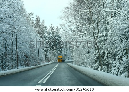 Yellow truck passing the snowy forest - stock photo