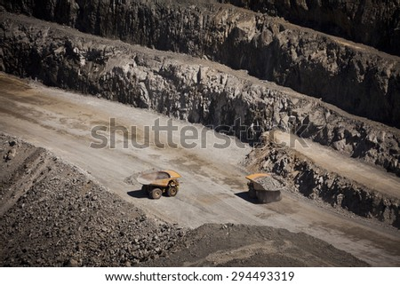 Yellow trucks inside an open cast mine in New South Wales, Australia. Barrick Cowal Gold Mine. - stock photo