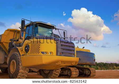 yellow trucks on a field with beautiful blue sky and clouds - stock photo