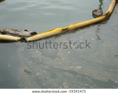yellow tube blocks out oily bubble material keeping water on other-side clean - stock photo