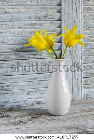 Yellow tulips in a white ceramic vase on blue wooden background. Still life in rustic vintage style - stock photo