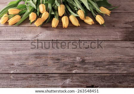 yellow tulips over wooden table background - stock photo