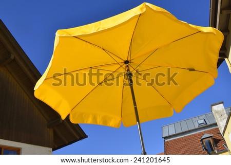 Yellow umbrella against blue sky - stock photo