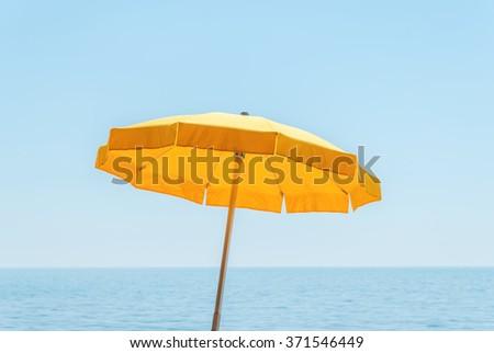 yellow umbrella near sea under blue sky - stock photo