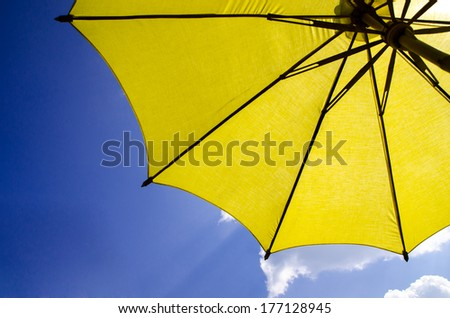 yellow umbrella on blue sky with clouds - stock photo