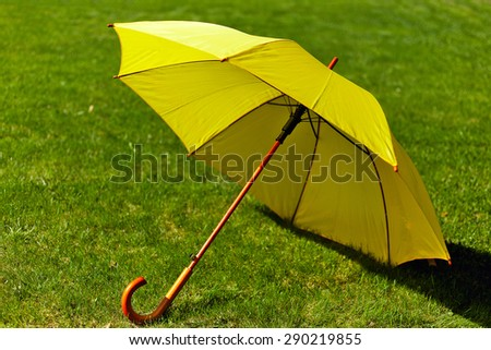 Yellow umbrella on the green grass - stock photo