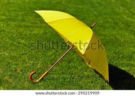 Yellow umbrella on the green grass - stock photo