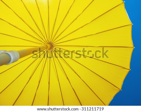 Yellow umbrella open against the sky. Protection shadow. Parasol - stock photo