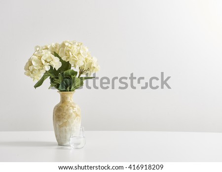 yellow vase yellow flower behind white wall  - stock photo