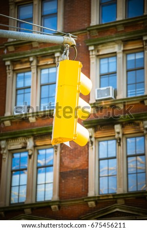Yellow vertical semaphore hanging on street pillar on background of building.