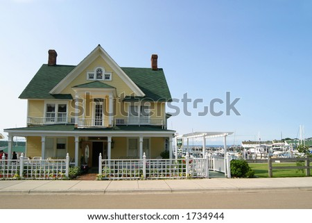 Yellow Victorian-style house with green roof.  Blue sky and marina with sailboats in background. - stock photo