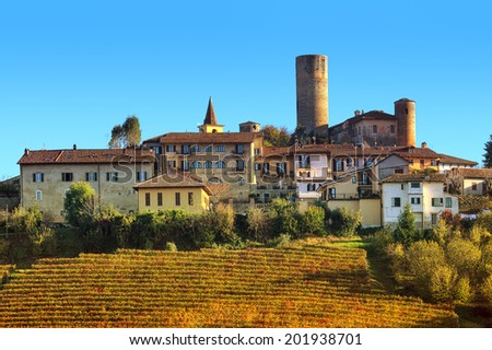Yellow vineyards and small medieval town on the hill in autumn in Piedmont, Northern Italy. - stock photo