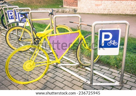 Yellow vintage bicycle in metal rack in the old town of Riga - stock photo
