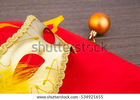 Yellow vintage mask with feather on red, festive object