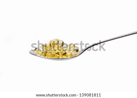yellow vitamin tablets, transparent yellow vitamin tablets with teaspoon - stock photo