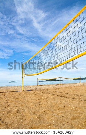 Yellow volleyball net and post on the beach  - stock photo