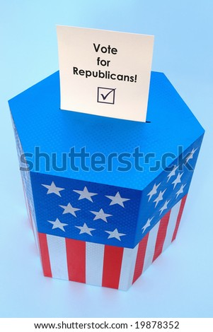 Yellow voting card with Vote for Republicans slogan half-inserted into ballot box decorated with american flag star and stripe colors over blue background - stock photo