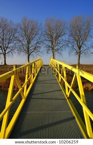 Yellow walking bridge with railing - stock photo