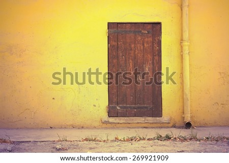 Yellow wall and an old wooden door in retro vintage style - stock photo