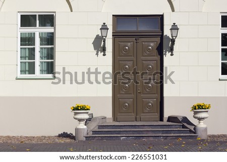 Yellow wall and old brown  wooden door, pansies in pots-  urban details background - stock photo