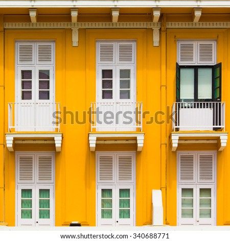 Yellow wall and white window in Singapore.