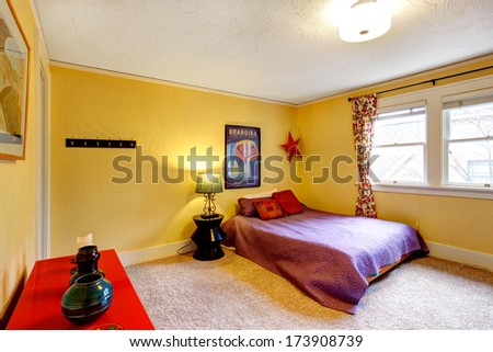 Yellow wall bedroom with bright red cabinet  and queen size bed - stock photo