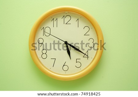 Yellow wall clock on the green background - stock photo