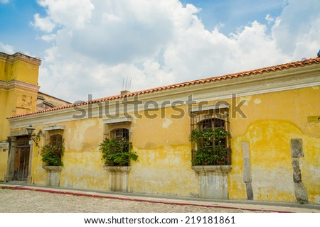 yellow wall colonial architecture in antigua city in guatemala - stock photo