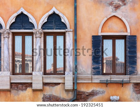 Yellow wall of antique Venetian building with old arched windows, rustic texture - stock photo