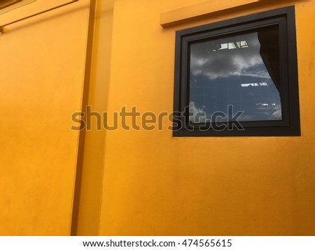 yellow wall with Black window and space for message