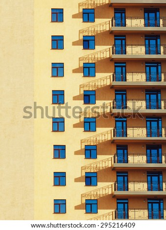 yellow wall with blue windows - stock photo
