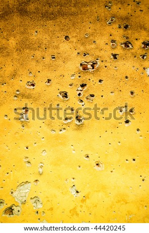 Yellow wall with bullet holes - stock photo