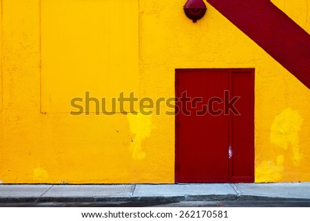 Yellow Wall with Red Door - stock photo