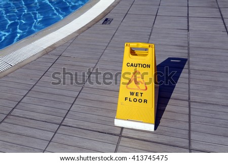 Yellow warning sign: ?aution, wet floor.