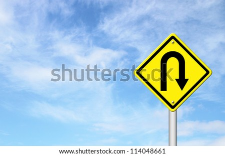 Yellow warning sign u-turn roadsign with blue sky background blank for text - stock photo