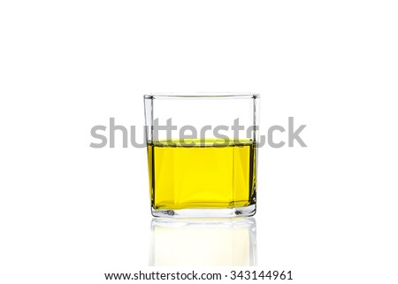 Yellow water in glass with reflection on white background
