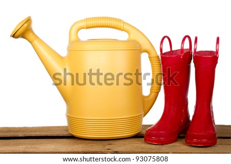 Yellow watering can and red boots on a wooden plank - stock photo