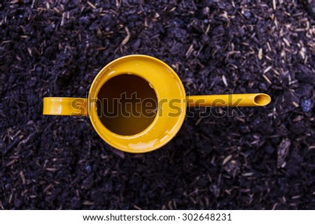 yellow watering can  on the ground.top view. - stock photo